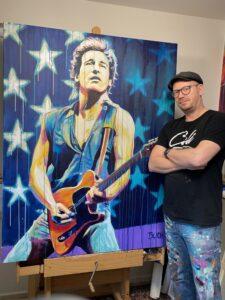 Original popart maleri af kendte amerikanske bruce springsteen med guitar og det amerikanske flag med løbende maling, malet af kunstner Allan Buch. Maleri til salg Maleri til salg
